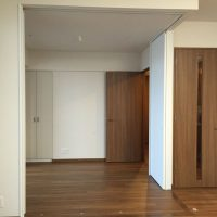 L字の可動間仕切り壁を全開した状態 リビング正面からの写真です 右にLDKに入る扉、奥に写っているのが洋室に入る扉